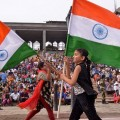 Young Indian tourists carry the national flag as they run prior to the Beating Retreat Ceremony at the India-Pakistan Wagah Border Post on March 24, 2016. / AFP / NARINDER NANU