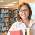In the library - Aisian female student with books working in a university library.